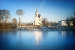 Church on the banks of the frozen river Stock Photos