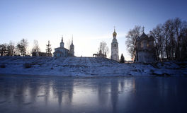 Church on the banks of the frozen river ice winter Stock Images