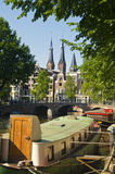 Church and barge in Amsterdam, Netherlands. Church and floating house in Amsterdam, Netherlands stock images