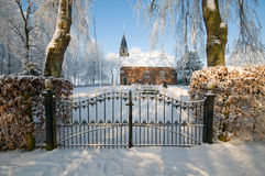 Church behind a fence in winter landscape Stock Photo