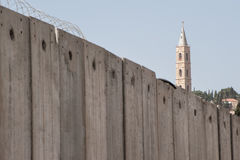 Church behind Israeli separation wall. The belltower of the Russian Orthodox Church of the Ascension rises above the Israeli separation wall that divides Royalty Free Stock Photography