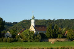 Church with belfry. And cross near the hill covered with woods, across green field in countyside Stock Photo