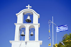 Church belfry and the greek flag waving Stock Image