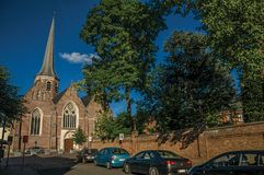 Church and belfry with trees at sunset in Tielt. Tielt, Belgium - July 02, 2017. Church and belfry with trees at sunset in Tielt. Charming and quiet village in Royalty Free Stock Photos