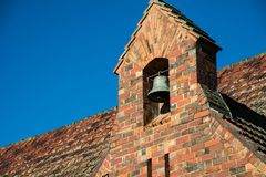 Church Bell. Nestiled in a brick arch, with tiled roof Royalty Free Stock Images