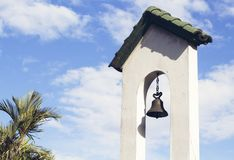 Church bell on church tower on blue sky background. Catholic church building. Stock Photo