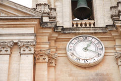 Church bell and clock. Close up of a church clock and church bell on a Maltese church Stock Image