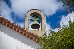 Church bell on the roof against a blue sky with white clouds and green foliage of olive trees around. Caldas de Monchique, Portugal Royalty Free Stock Photography