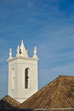 Church bell tower behind tiled roof Stock Photo