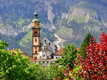 Church with bell tower, colorful leaves and mountains Stock Photos