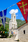 Church bell tower and flags on the island of Ioannina, lake Ioan Royalty Free Stock Photo