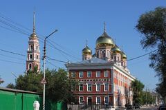 Church and bell tower with golden domes. Church in the city, facing the street. Stock Photo