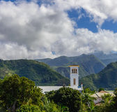 Church with bell tower in l'Entre-Deux with mountains in backgro Stock Photography