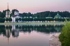 Church with bell tower next to the pond and park pavilion `Grotto` in museum-estate Kuskovo, Moscow. Stock Images