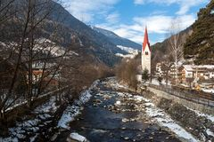 Church with a bell tower on the river Ahr. Campo Tures Stock Photo