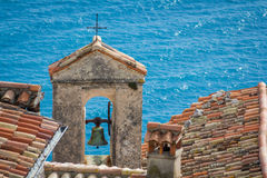 Church bell tower and rooftops. With blue sea in the background Royalty Free Stock Images