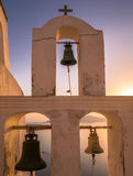 Church Bell Tower at Sunset in Santorini, Greece. Backlit church bell tower with three bells overlooking Athinios Bay and the island of Nea Kameni in the evening Royalty Free Stock Images