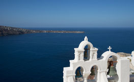 Church bells in Ia, Santorini, Greece. Overlooking the sea to Therisia Royalty Free Stock Photography