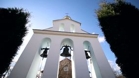 Church bells on a Sunny day in a strong wind. The wind shakes the trees near the bell tower and Sonechka shines in the stock footage