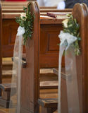 Church bench decoration. Flower arrangements for wedding in a church on side of pew with singing book on the bench Stock Photography
