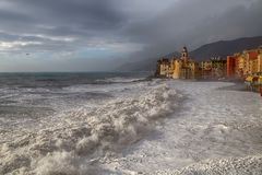 The church and the big wave in Camogli Genoa, Italy. royalty free stock photo