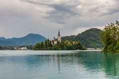 Church on the Bled lake island. Dark gray sky after storm . royalty free stock photo