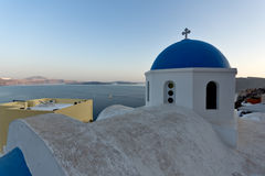 Church with blue roof in town of Oia and panorama to Santorini island, Thira, Greece. Church with blue roof in town of Oia and panorama to Santorini island Stock Images