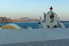 Church with blue roof in town of Oia and panorama to Santorini island, Thira, Greece. Church with blue roof in town of Oia and panorama to Santorini island Stock Photo