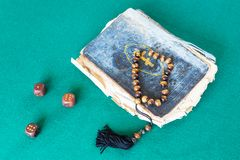 Church book, worry beads and three wooden dices. Old church book, worry beads and three wooden dices on green baize table stock photos