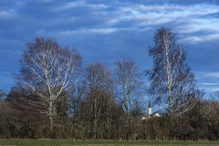 Church between branches and trees with two birches. White church between branches behind shrubbery , trees and two sunny birches and cloudy sky Stock Photos