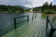Church and bridge in Bohinj lake Stock Image