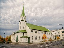 Church building on cloudy sky in Reykjavik, Iceland. Church building with white walls and green roof on cloudy sky in Reykjavik, Iceland. Architecture, landmark stock images