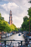 Church and canal in Amsterdam, Netherlands. Church and canal with boats and barges in Amsterdam, Netherlands Stock Images