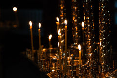 Church candles burn in a candlestick against the backdrop of ico Royalty Free Stock Images
