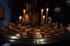 Church candles burn in a candlestick against the backdrop of ico Stock Photography