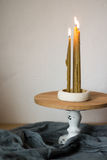 Church candles burn on a white background. Long lighted candles group on wooden board with natural cotton cloth on white background. Holiday, church concept Royalty Free Stock Image