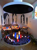 Lighted candles and statues in chapel. Lighted candles and statues in a chapel in the city of Sete, France stock photo