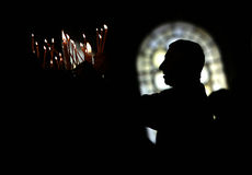 Church candles person silhouette. A man is lighting candles in a church at Easter Stock Photography
