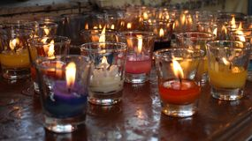 Church candles in red and yellow transparent chandeliers stock image