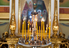 Church candles standing in the temple on the stand during the service. stock photo