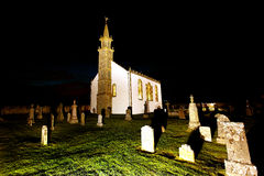 Church and cemetery at night. Small church and cemetery illuminated at night, Scotland Stock Images