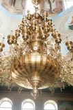 Church chandelier on wall with gold natural light Stock Images