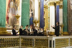Church choir with conductor singing during the church service. In Saint Isaac`s orthodox cathedral royalty free stock photography