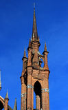 Church in the City. Stone church tower against a blue sky Royalty Free Stock Photo