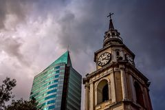 Church clock tower and highrise apartment in Chile. Old church clock tower and modern highrise apartment in Chile in Santiago, Chile Royalty Free Stock Images