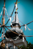 Church clock tower through street chandelier Royalty Free Stock Photo