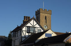Church clock tower with timber building. Church clock tower with tudor style timber building infront Stock Photo