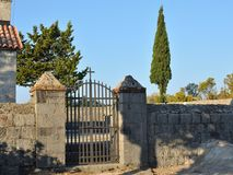 Church closed gate. Closed church iron gate with tree tops in a church yard Royalty Free Stock Photography