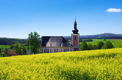 Church on the colza field Royalty Free Stock Photography