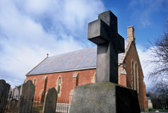 Church and Cross. Close up of stone cross in Church Cemetery, with red brick Church in background Stock Photography